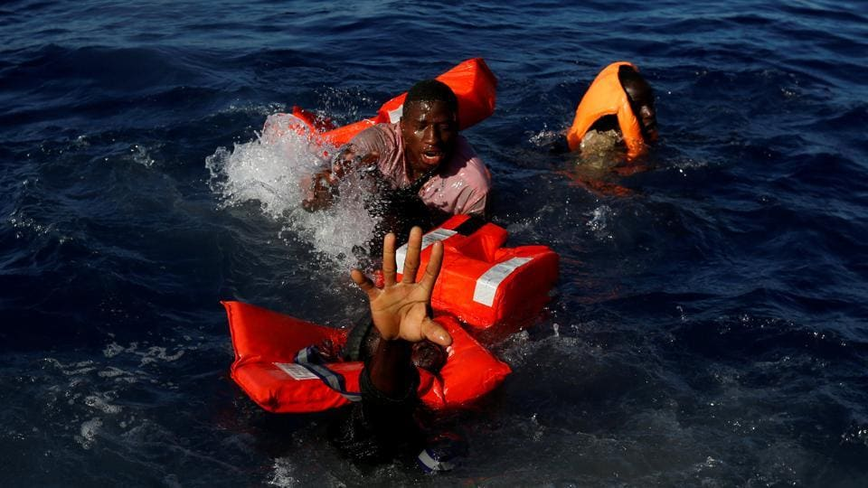 Migrants try to stay afloat after falling off their rubber dinghy during a rescue operation by the Malta-based NGO Migrant Offshore Aid Station (MOAS) ship in the central Mediterranean in international waters some 15 nautical miles off the coast of Zawiya in Libya on April 14, 2017. All 134 sub-Saharan migrants survived and were rescued by MOAS.  (Darrin Zammit/REUTERS)