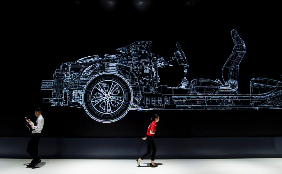 A man and a woman walk under an advertisement for Japanese carmaker Toyota during the first day of the 17th Shanghai International Automobile Industry Exhibition in Shanghai on April 19, 2017.
