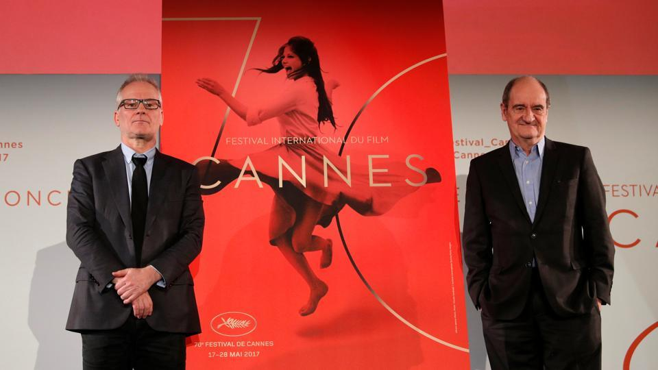 Cannes Film festival general delegate Thierry Fremaux (L) and Cannes Film festival president Pierre Lescure (R) pose in front of the official poster for the 70th Cannes Film Festival after a news conference, to announce this year's official selection in Paris, France, April 13, 2017.