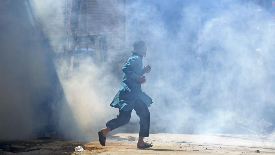 A Kashmiri protester runs after forces fired tear smoke shells during clashes in downtown Srinagar.