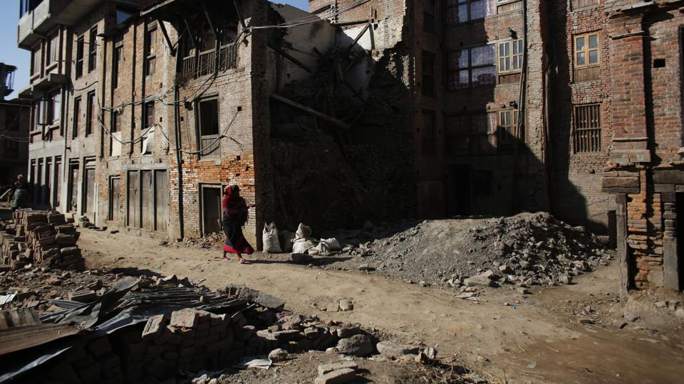File photo of a woman walking past houses damaged in the 2015 earthquake in Bhaktapur, Nepal, in January 2017. Hundreds of houses were damaged during the April 25, 2015 earthquake in Bhaktapur, known for brick paved roads, old palaces and artistic Hindu temples.