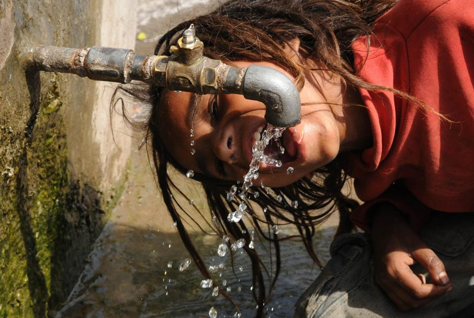 Patiala, India-23 April 2017::::A boy drinks dripping water from a public tap in tractor market in Patiala on Sunday, April 23, 2017.Photo by Bharat Bhushan Hindustan Times.