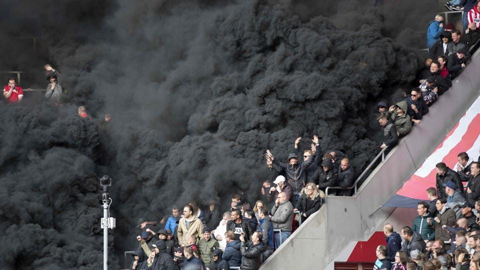 Black smoke engulfs the tribune during the PSV Eindhoven vs AFC Ajax Eredivisie football match in Eindhoven on Sunday.