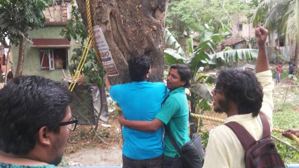 Students hugging a tree and shouting slogans on NH112 as the administration gets ready to fell it.