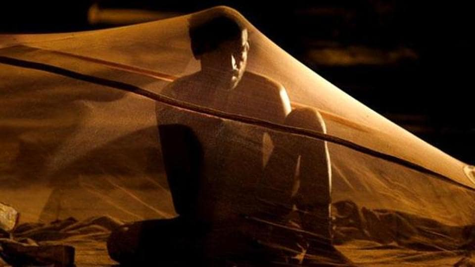 A rickshaw-puller prepares to sleep under a mosquito net in the national capital.