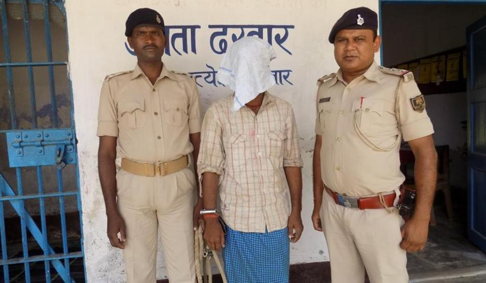 Mangal Sharma (face covered), an accused in the killing of his two-year-old son, with cops in Purnia.
