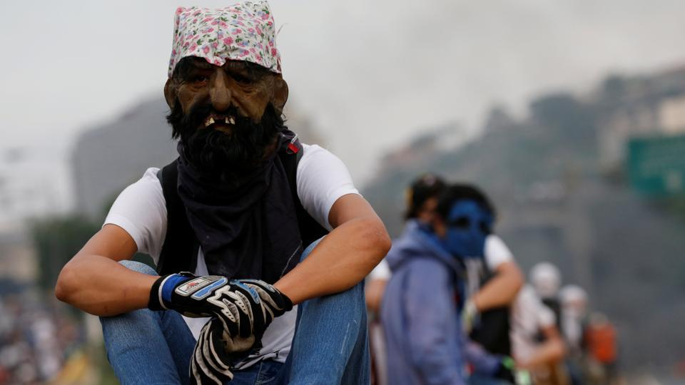 A demonstrator uses a mask during the rally. Maduro won the 2013 election by a narrow margin over opposition candidate Henrique Capriles. But Maduro's popularity has since dropped. (Carlos Garcia Rawlins/REUTERS)