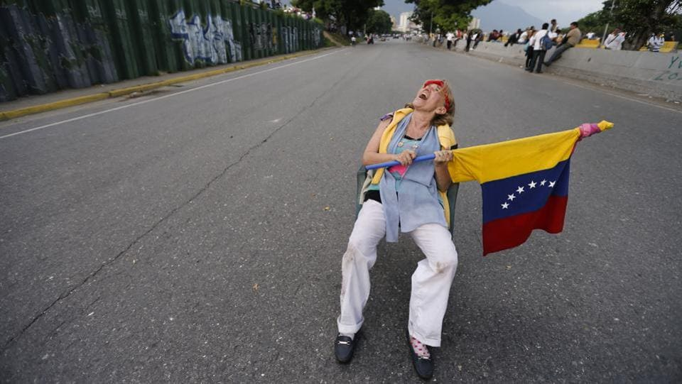 A woman sits on a highway ramp as anti-government protesters stage sit-ins to disrupt traffic throughout Caracas. The courts and electoral authorities have fended off efforts to remove Maduro since the opposition took over the legislature in January 2016. (Ariana Cubillos/AP)