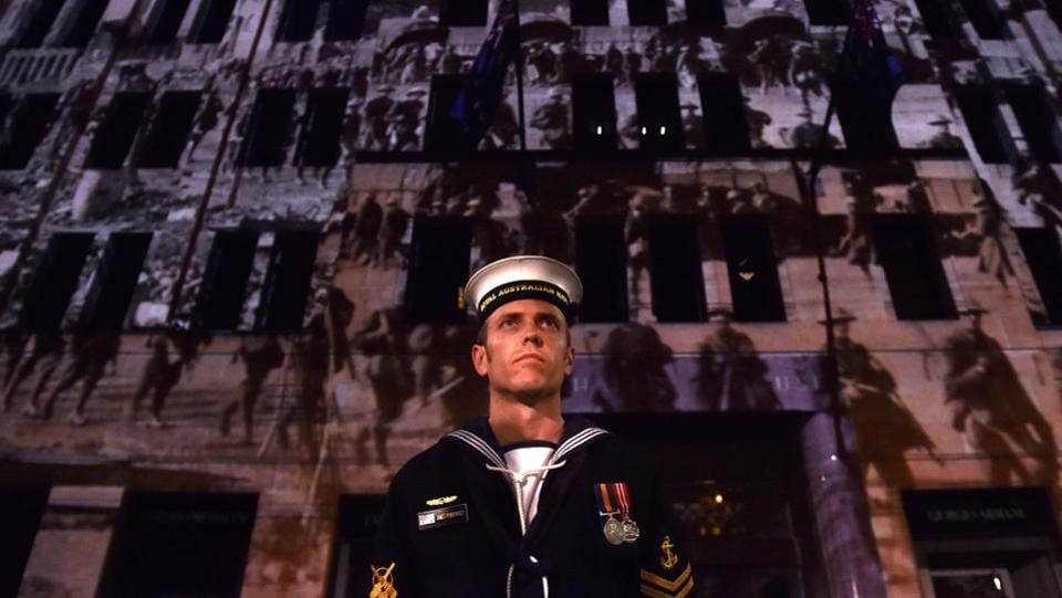 A serviceman stands in front of a building projecting world war pictures near the Cenotaph during the Anzac Day Dawn Service in Sydney. Dawn services were held across the two countries on the anniversary of the ill-fated 1915 campaign of the Australian and New Zealand Army Corps that left 11,500 of them dead in what is now Turkey during World War I. (Saeed Khan/AFP)