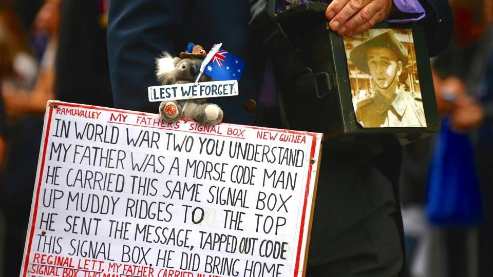 A relative of a veteran carries a sign and photograph as a tribute. Drawing attention to the current batch of troops returning from Afghanistan and Iraq, Curtis McGrath spoke of how his friends fought to save him in 2012 after an explosion blew off his legs. (David Gray/REUTERS)