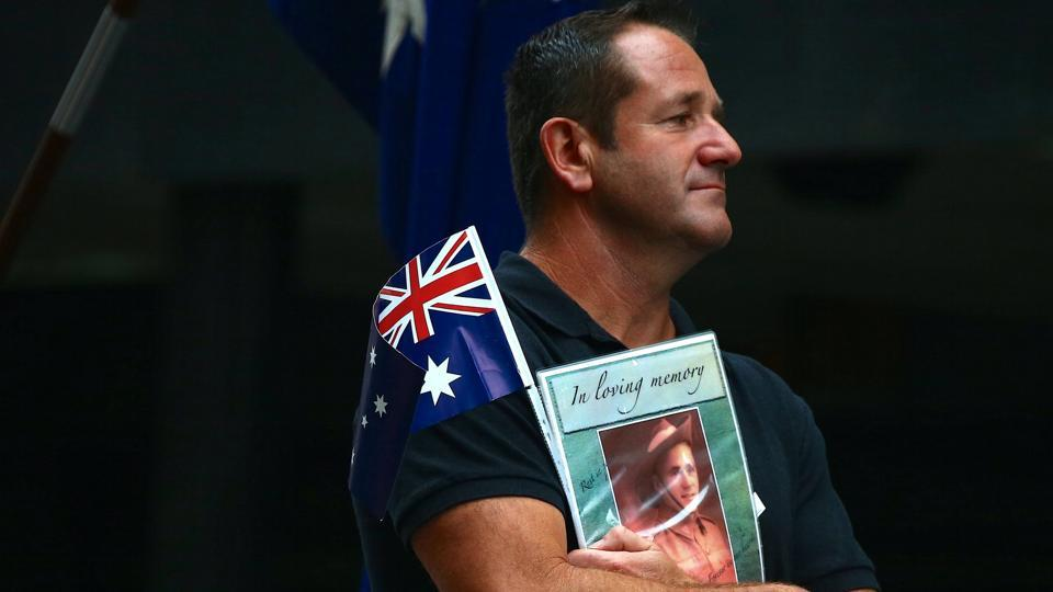 A relative of a veteran carries an Australian national flag and photograph as a tribute. Forty-two Australians have died while on military service in Afghanistan and two in Iraq since 2002. (David Gray/REUTERS)