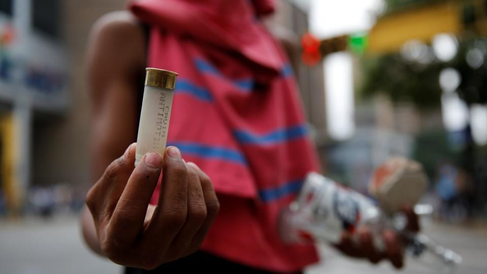 A demonstrator shows an empty shotgun shell during a rally in Caracas. (Carlos Garcia Rawlins/REUTERS)