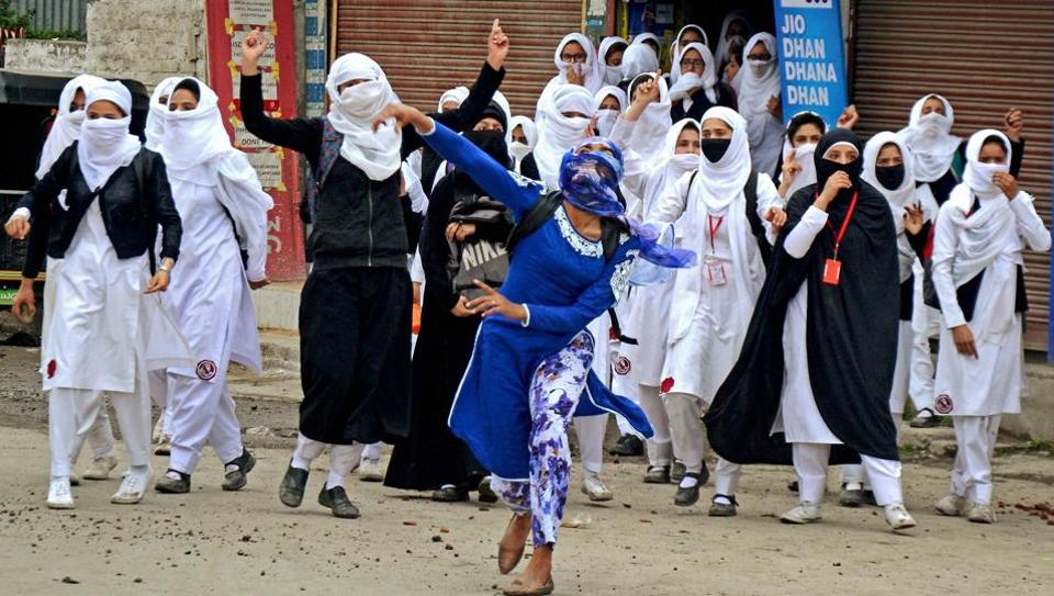 Girl students pelt stones at security personnel during clashes in Lal Chowk in Srinagar.