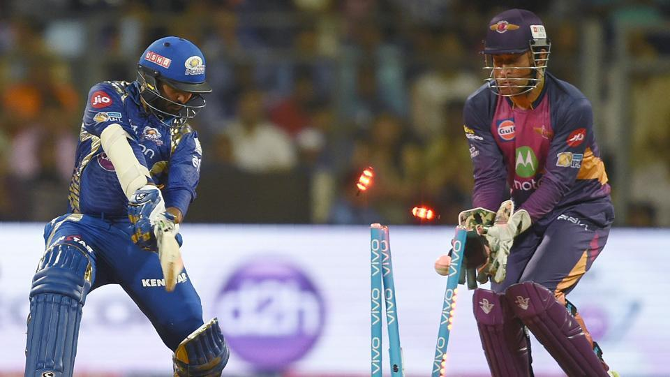 Mumbai Indians cricketer Parthiv Patel is bowled out as Rising Pune Supergiants cricketer Mahendra Singh Dhoni looks on. (AFP)