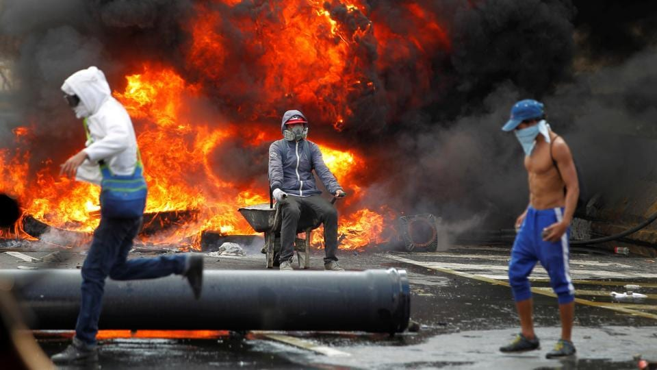Demonstrators build a fire barricade on a street. Latin American countries and the United States have voiced concern at the unrest. (Christian Veron/REUTERS)