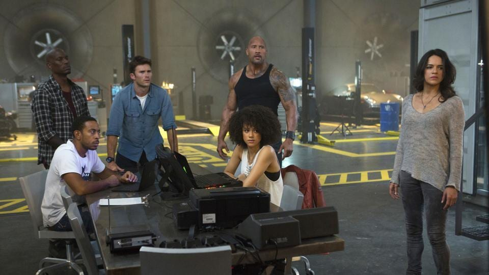 This image released by Universal Pictures shows, Chris Ludacris Bridges, seated left, and Nathalie Emmanuel, seated right, and Tyrese Gibson, standing from left, Scott Eastwood, Dwayne Johnson and Michelle Rodriguez in The Fate of the Furious.