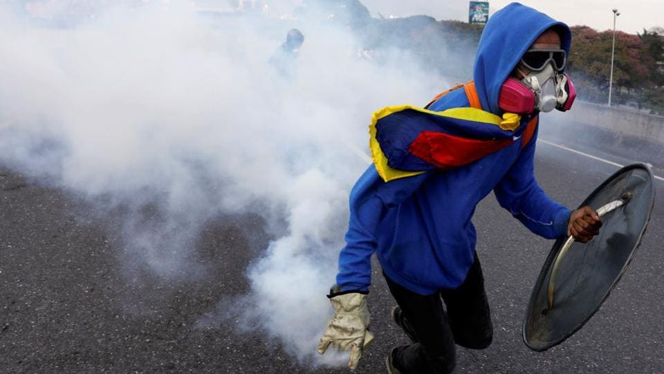 A demonstrator throws back a tear gas grenade at the riot police while rallying. (Garcia Rawlins/REUTERS)