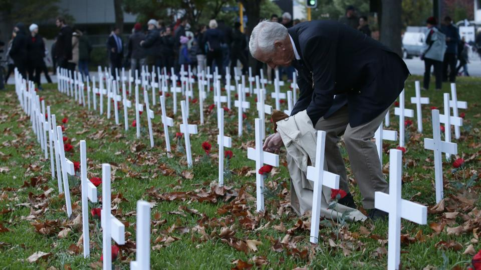 A man places a poppy on a cross at the field of remembrance following the ANZAC Day dawn service in Christchurch, New Zealand. (Mark Baker/AP)