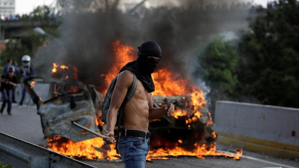 A demonstrator stands near fire. The government has ruled out a presidential election this year, maintaining that Maduro will see out his term into 2018.  (Carlos Garcia Rawlins/REUTERS)