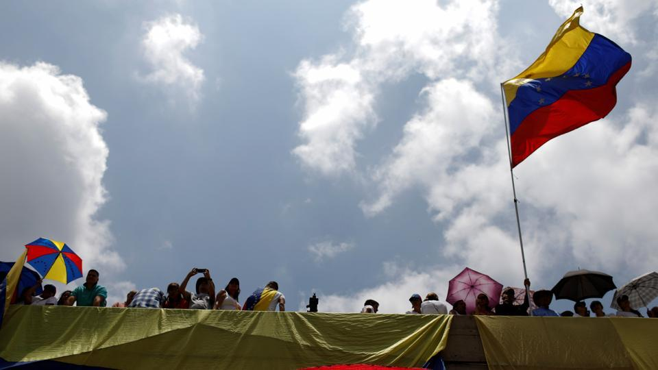 Opposition supporters wave Venezuelan national flags during a rally. (Carlos Garcia/REUTERS)