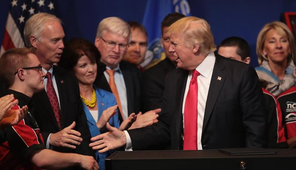 President Donald Trump greets VIPs after speaking at the headquarters of tool manufacturer Snap-On on April 18, 2017 in Kenosha, Wisconsin. During the visit, Trump signed an executive order to try to bring jobs back to American workers and revamp the H-1B visa guest worker programme.