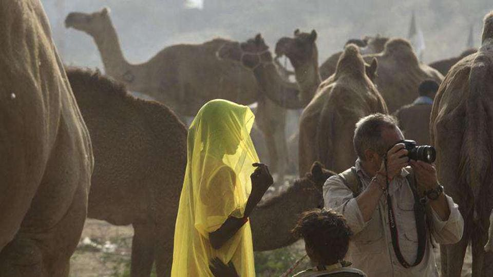 A woman walks past camels as a foreign tourist takes pictures at the Pushkar fair in Pushkar, Rajasthan. Pushkar, located on the banks of Pushkar Lake, is a popular Hindu pilgrimage spot that is also frequented by foreign tourists for its annual cattle fair and camel races.