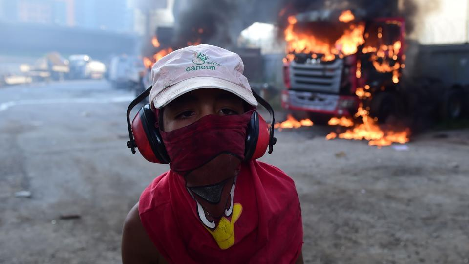 A hooded young boy is pictured near burning trucks during a demonstration by Venezuelan opposition activists. Riot police fired rubber bullets and tear gas to break up one of the first rallies in eastern Caracas early Monday while other groups were gathering elsewhere, the opposition said.  (Ronaldo Schemidt/AFP)