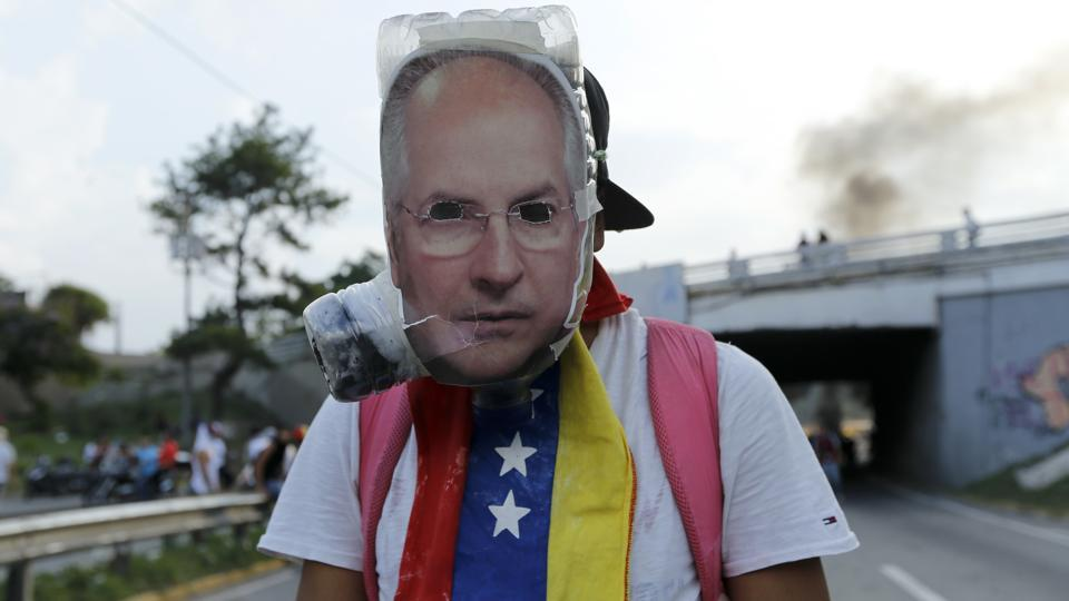An anti-government protester wears a mask with the image of jailed opposition leader Antonio Ledezma. The conservative-led opposition says government incompetence is to blame and calls the elected president a dictator. It wants early elections. But Maduro, who has the backing of the armed forces, says Venezuela is the victim of a US-led capitalist plot.  (Ariana Cubillos/AP)