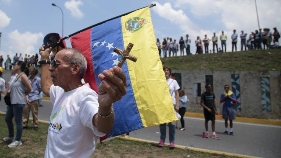 A man holds a crucifix and a Venezuelan flag as anti-government protesters block a highway in Caracas. Thousands of protesters shut down the capital city's main highway to express their disgust with the socialist administration of President Nicolas Maduro. Protesters in least a dozen other cities also staged sit-ins as the protest movement is entering its fourth week.  (Fernando Llano/AP)