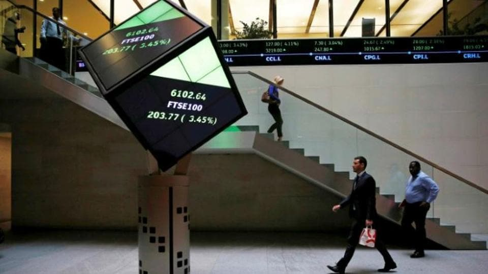 People walk through the lobby of the London Stock Exchange in London, Britain August 25, 2015.