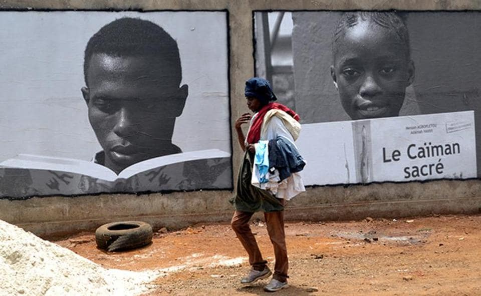 Conakry is hosting UNESCO's World Book Capital for one year as from April 23, 2017. A person walks past posters promoting the event in Conakry on Sunday.