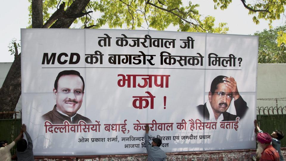 Workers put up a hoarding outside Delhi BJP headquarters in New Delhi on Wednesday after the party won the MCD elections.