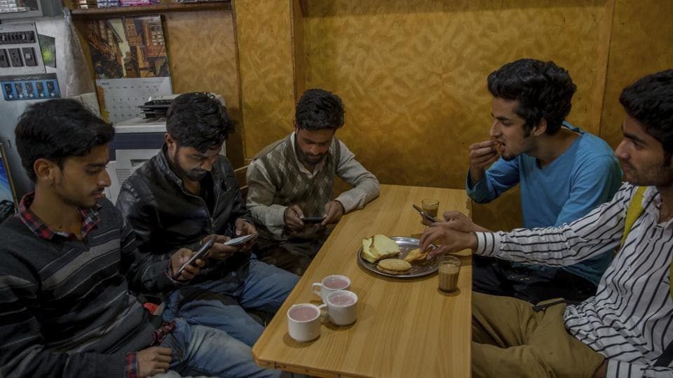 Kashmiri students browse the internet on their mobile phones at a restaurant in Srinagar on Wednesday. The authorities ordered a suspension of 22 social media sites, including Facebook and Twitter.