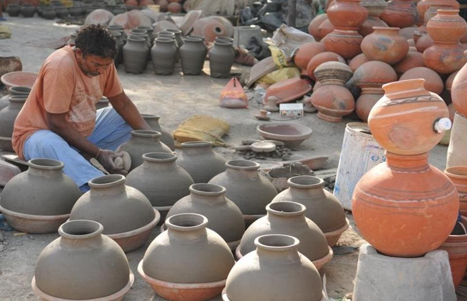 A potter working on earthen water coolers in Mansoorwal village on the outskirts of Kapurthala on Wednesday, April 26. (Pardeep Pandit/HT)