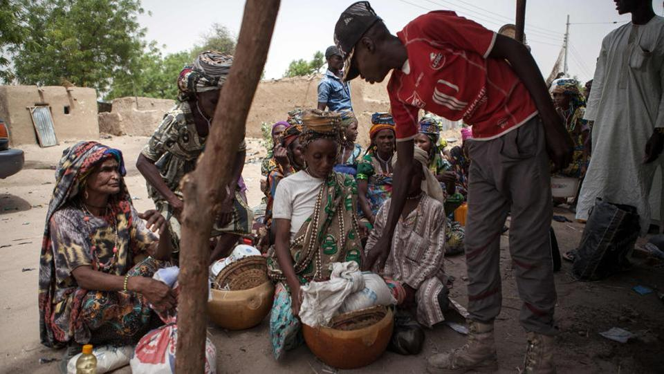 A member of Civilian Joint Task Force (CJTF) screens women at the entrance of the town of Damasak in North East Nigeria on April, 25 2017 as thousands of Nigerians, who were freed in 2016 by the Nigerian army from Boko Haram insurgents, are returning to their homes .  (Florian Plaucheur / AFP)