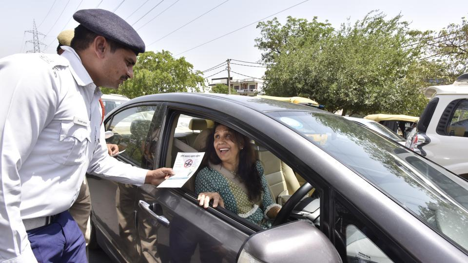 Traffic police officials distributing pamphlets to raise awareness about the dangers of honking.