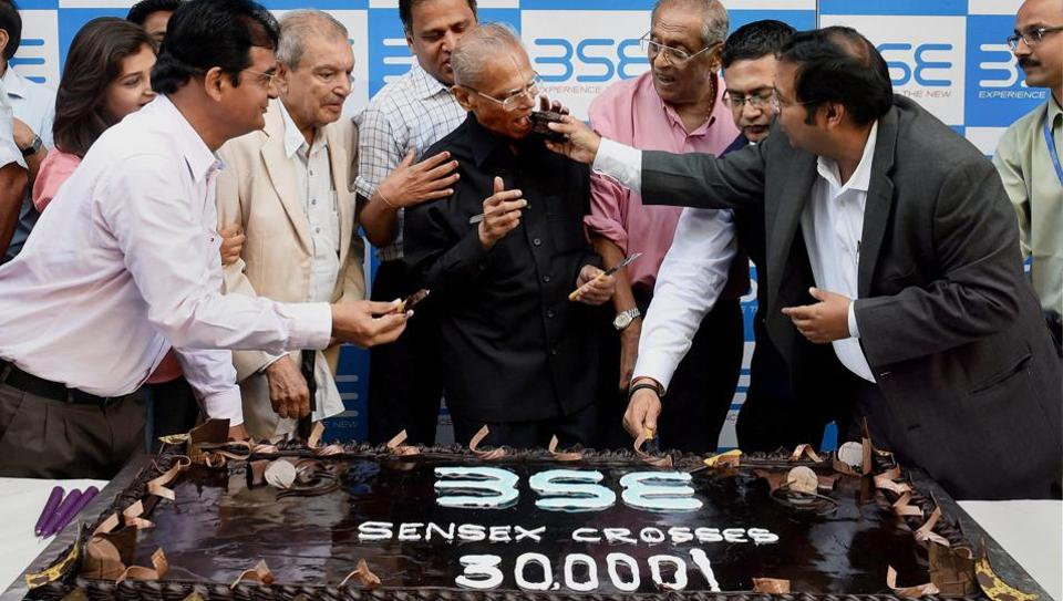 A cake weighing 30 kg is cut as part of celebrations outside BSE as Sensex crossed 30k mark in Mumbai on Wednesday.