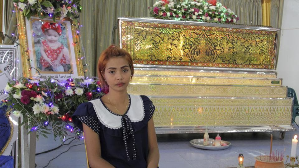 Chiranut Trairat, mother of an 11-month-old baby girl, sits in front of her daughter's coffin at Si Sunthon temple in Phuket, Thailand.