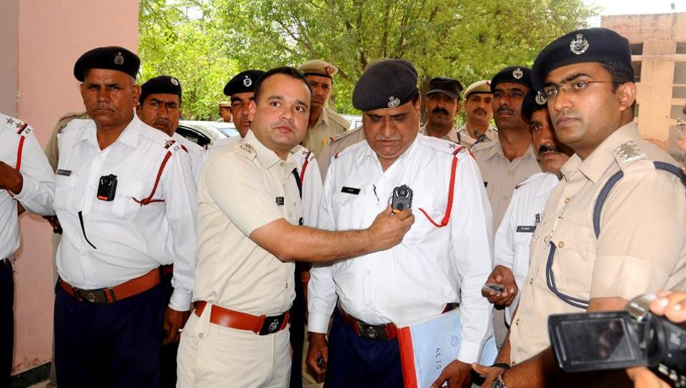 Rohtak superintendent of police Pankaj Nain fitting a body camera on a traffic cop in Rohtak on Tuesday .