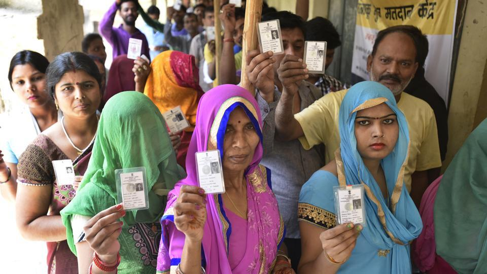 Voters stand in queue at a polling station during the MCD election in New Delhi on April 23.