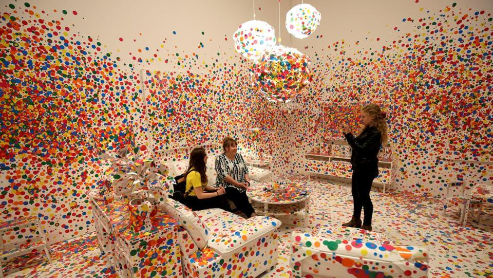 People inside 'The Obliteration Room'.The rooms use facing mirrors, hanging lights and polka dots to create vistas of infinite regress. (Joshua Roberts / Reuters)