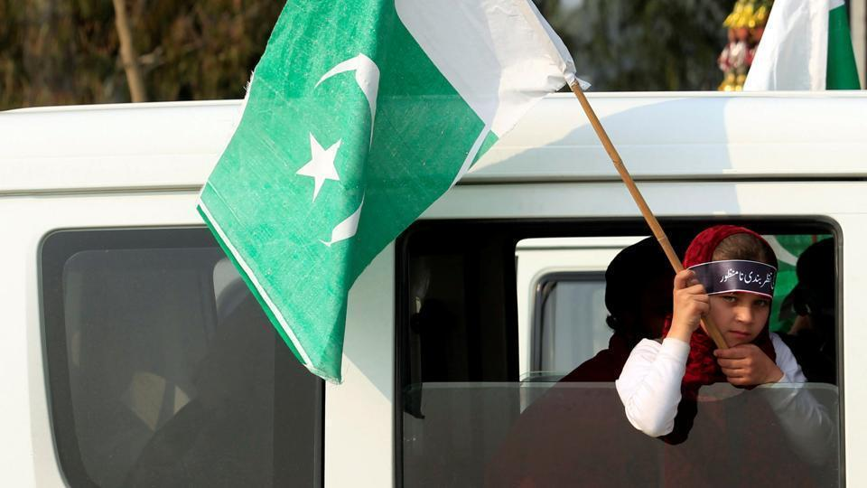 A girl holds a Pakistani flag during a rally.