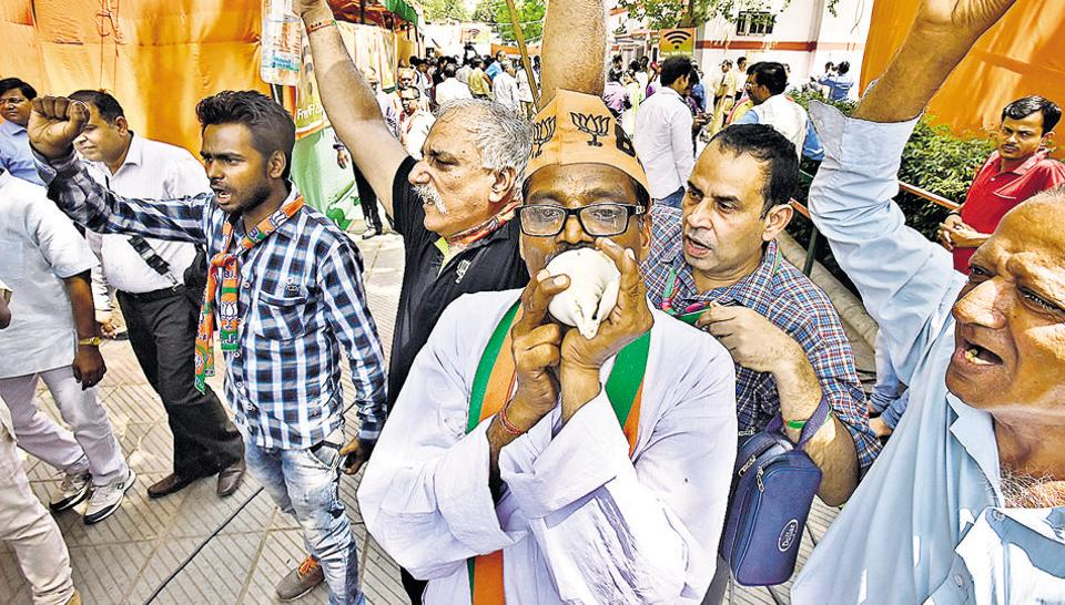 BJP party workers shout slogans outside the party office at Delhi's Pandit Pant Marg after MCD results were declared on April 26.