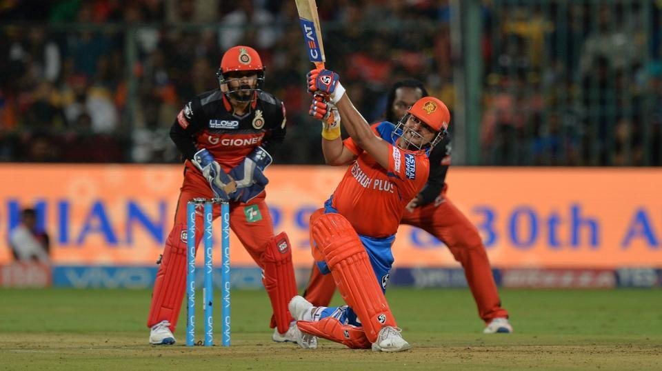 Royal Challengers Bangalore wicket keeper Kedar Jadhav (L) looks on while Gujarat Lions captain and batsman Suresh Raina (C) plays a shot during their 2017 Indian Premier League (IPL) match at the Chinnaswamy Stadium in Bangalore. Live streaming of the IPL T20 match between Royal Challengers Bangalore vs Gujarat Lions was available online.