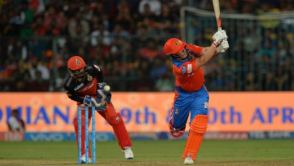 Royal Challengers Bangalore wicket keeper Kedar Jadhav (L) looks on as Gujarat Lions batsman Aaron Finch (R) plays a shot during their 2017 Indian Premier League (IPL) match at the Chinnaswamy Stadium in Bangalore on April 27.