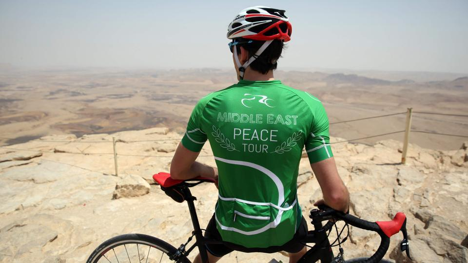 A cyclist stands on the cliff of the Machtesh Ramon crater, near the town of Mitzpe Ramon in the southern Israeli Negev desert, after riding on the fourth day of the Middle East Peace Tour. (MENAHEM KAHANA / AFP)