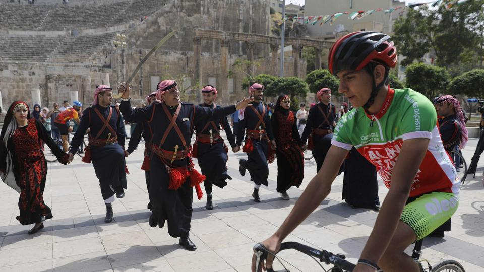 A cyclist rides past a group of traditional dancers at the ancient Roman theatre in the centre of Amman during a welcome ceremony for members of the Middle East Peace Tour. (MENAHEM KAHANA / AFP)