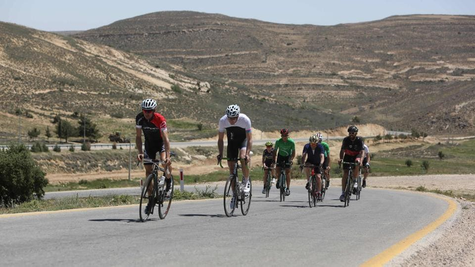 Foreign cyclists ride along a road leading to Petra. (MENAHEM KAHANA / AFP)