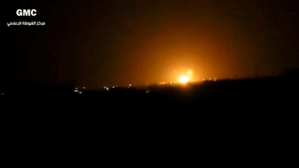 A still image from a video posted to social media and, said to be shot on April 27, 2017, shows explosions and rising flames amid lights in distance. The video was said to be shot in Damascus, Syria.
