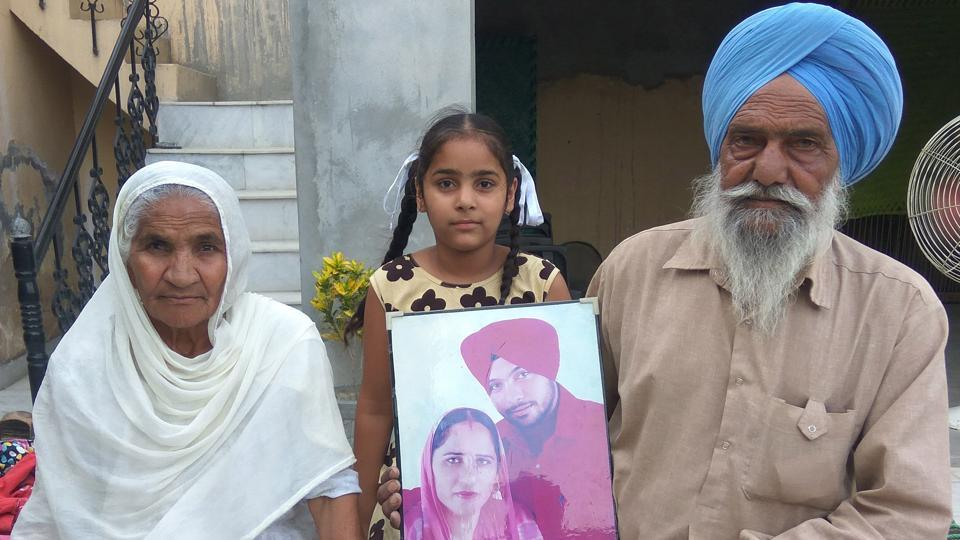 Joginder Singh and Gurbachan Kaur showing the picture of their son Jagtar Singh at Hamira village in Kapurthala on Wednesday.